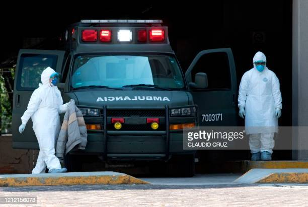 Medical personnel wear protective suits next to an ambulance outside the Belisario Dominguez Hospital in Mexico City on May 05 2020 The desperate...