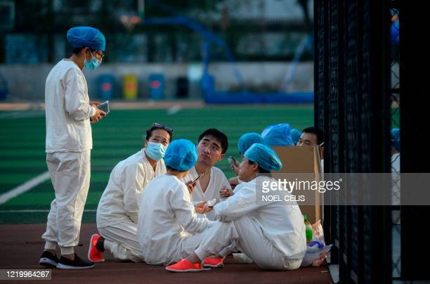 Medical personnel wearing a protective suit eat at the Guang'an Sport Center before a swab test for people who visited or live near Xinfadi Market in...
