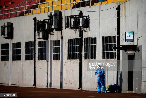 TOPSHOT Medical personnel wearing a protective suit is seen at the Guang'an Sport Center before a swab test for the people who visited or live near...