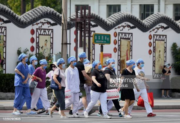 TOPSHOT Medical personnel wearing face masks arrive at a swab testing facility to test people who live near or who have visited the Xinfadi Market a...