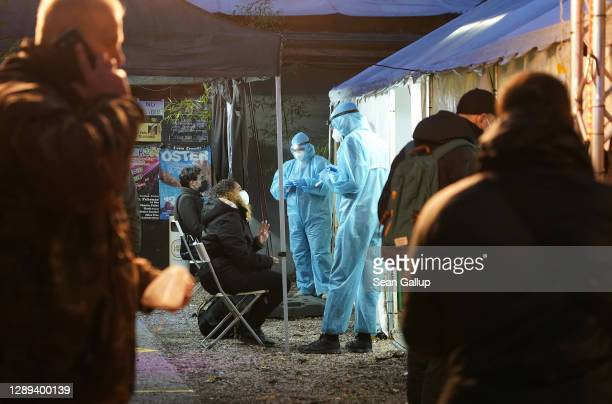 Medical personnel wearing PPE take throat swab samples from people seeking a rapid antigen Covid test at a testing station set up on the grounds of...