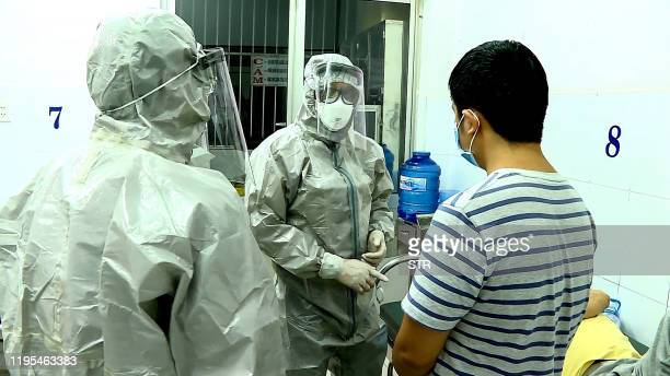 TOPSHOT Medical personnel wearing protectice suits interact with two patients tested positive to the coronavirus in an isolation room at Cho Ray...
