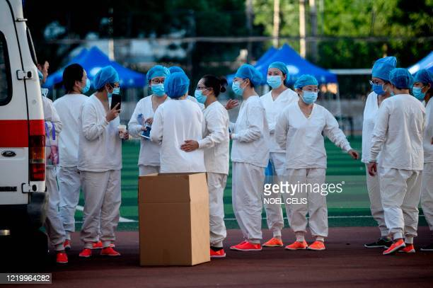 Medical personnel wearing protective suits gather at the Guang'an Sport Center before a swab test for people who visited or live near Xinfadi Market...