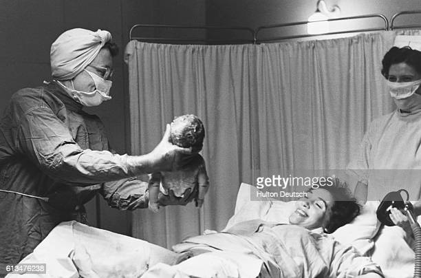A medical practitioner hands the newborn baby to it's mother after childbirth The mother had used analgesia during labour as an alternative to an...