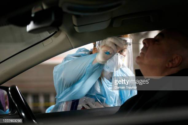 Medical practitioner performs a COVID-19 test on a member of the public at a drive through testing clinic in the carpark of Victoria Gardens Shopping...