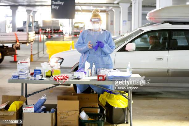 A medical practitioner prepares to administer a test on a member of the public at a drive through testing clinic in the carpark of Bunnings in West...