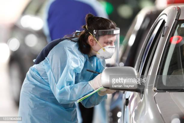 Medical practitioners take information from members of the public at a drive through testing clinic in the carpark of Victoria Gardens Shopping...