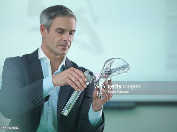 medical product designer inspecting hip joint model - hip replacement stock pictures, royalty-free photos & images