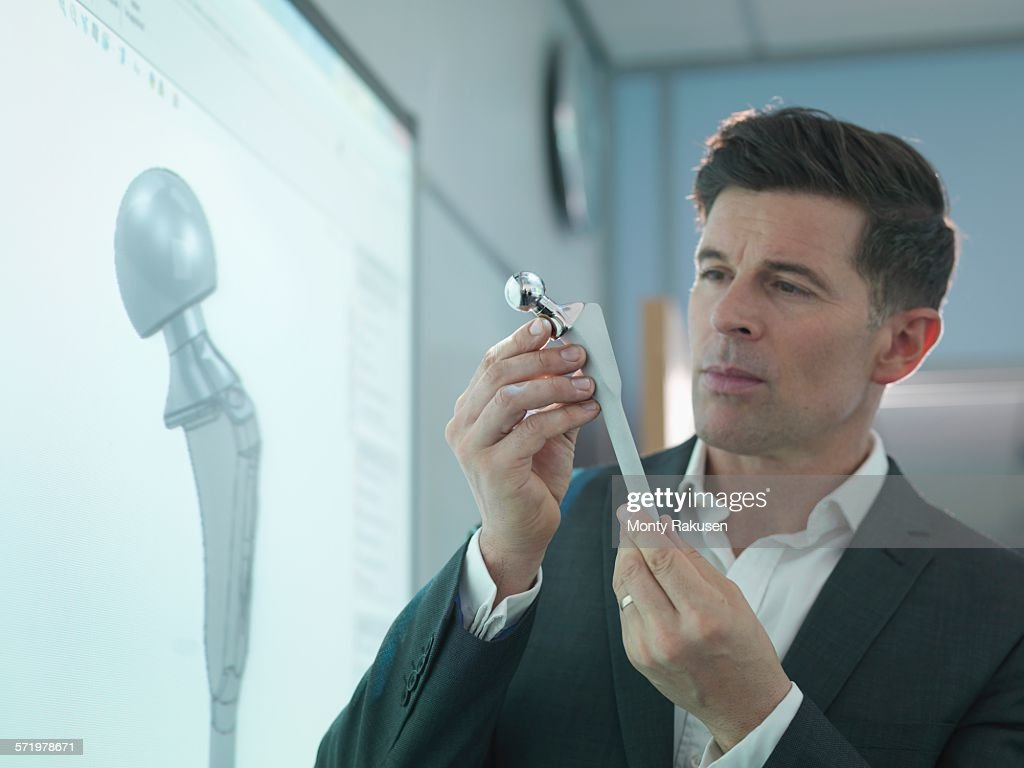 Medical product designer inspecting hip joint model with graphical screen : Stock Photo