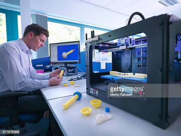Medical product designer with 3D printing machine with CAD design on screen in orthopaedic factory