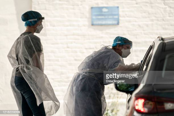 Medical professional administers a coronavirus test at a drive-thru testing site run by George Washington University Hospital, May 26, 2020 in...