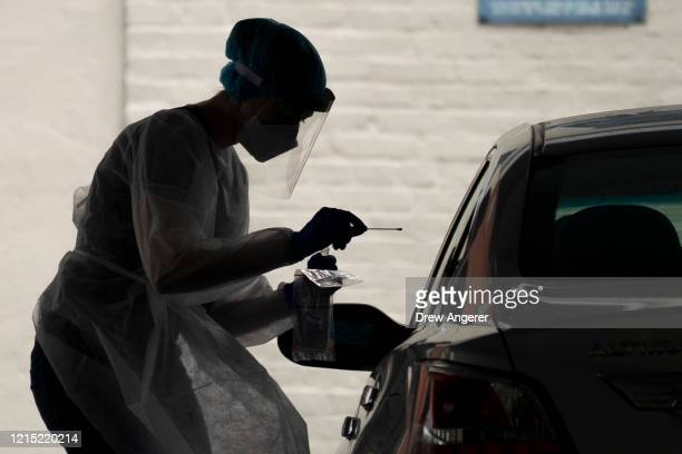 A medical professional administers a coronavirus test at a drivethru testing site run by George Washington University Hospital May 26 2020 in...