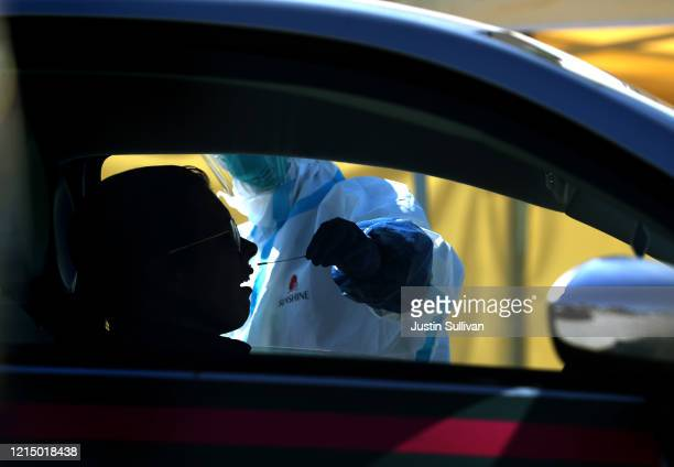 Medical professional administers a coronavirus test during a drive-thru testing station on March 26, 2020 in Daly City, California. New coronavirus...