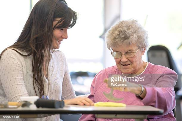 Medical professional and elderly woman smiling during physical therapy
