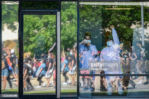 A medical professional at a plasma center holds her fist in the air as people marching to demand justice for Elijah McClain pass by the facility on...