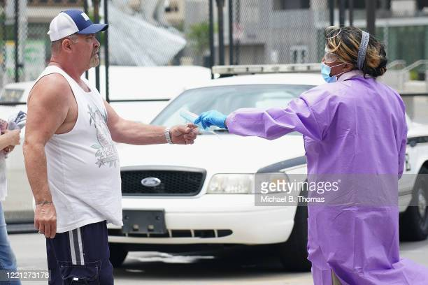 A medical professional distributes required masks to attendees prior to entering a political rally for President Donald Trump on June 20 2020 in...