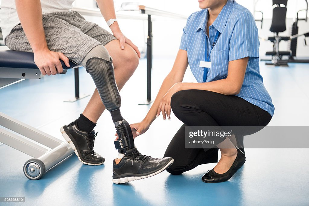 Medical professional helping man with prosthetic leg : Stock Photo