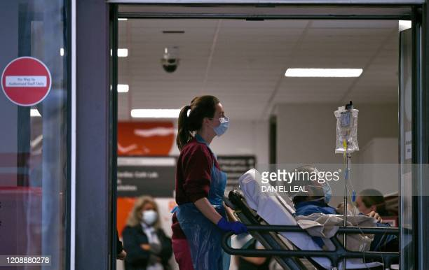 Medical professional in PPE, including gloves, an apron and a face mask as a precautionary measure against Covid-19, pushes a patient, also waering a...
