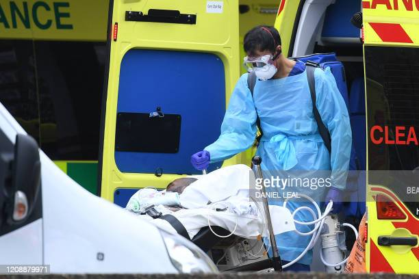 A medical professional in PPE including gloves eye protection and a face mask as a precautionary measure against Covid19 carries a tank as a patient...