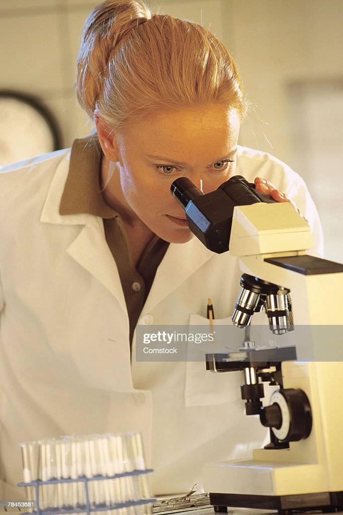 Medical professional looking into microscope : Stockfoto