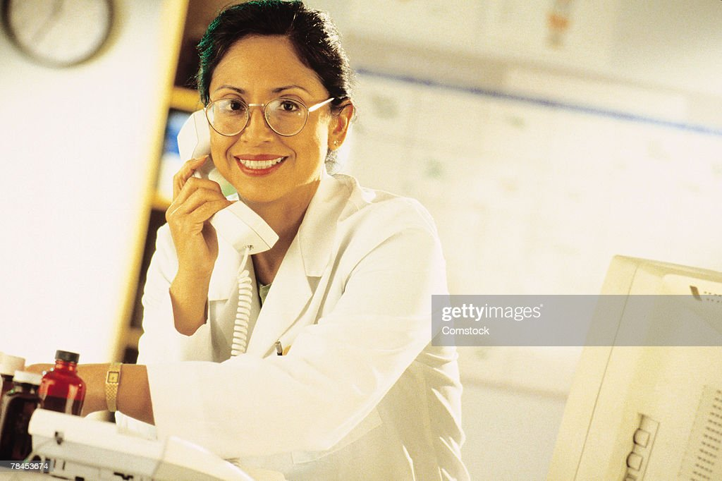 Medical professional on phone in her office : Stockfoto