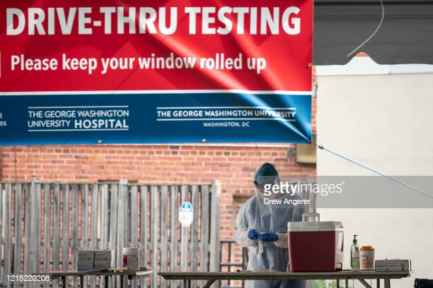 Medical professional prepares to administer a coronavirus test at a drive-thru testing site run by George Washington University Hospital, May 26,...