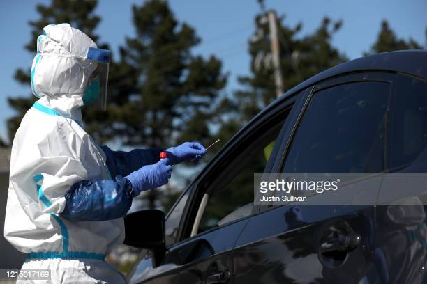 Medical professional prepares to administer a coronavirus test during a drive-thru testing station on March 26, 2020 in Daly City, California. New...
