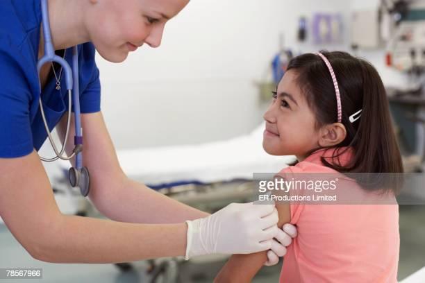 Medical professional preparing girl's arm for shot