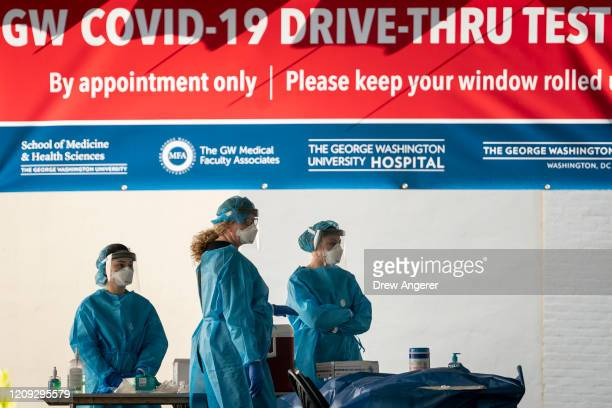 Medical professional wait for patients to arrive at a drivethru coronavirus testing site run by George Washington University Hospital on April 6 2020...