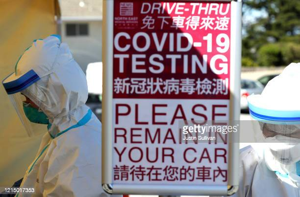 Medical professional wait to administer a coronavirus test during a drive-thru testing station on March 26, 2020 in Daly City, California. New...
