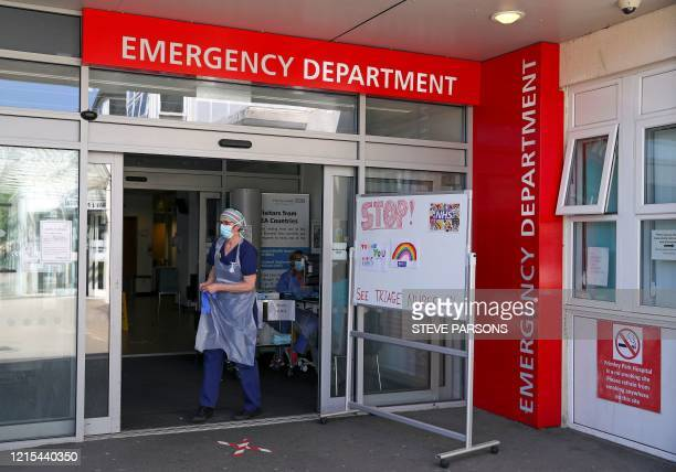 A medical professional wearing PPE including a face mask and plastic apron as a precautionary measure against COVID19 waits triage patients at the...