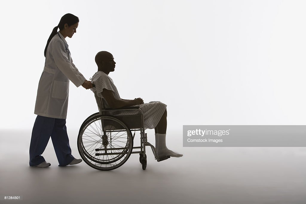 Medical professional with patient in wheelchair : Stock Photo