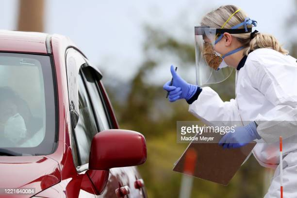 A medical professional works at a drivethru coronavirus testing site at Cambridge Health Alliance Somerville Hospital on April 28 2020 in Somerville...