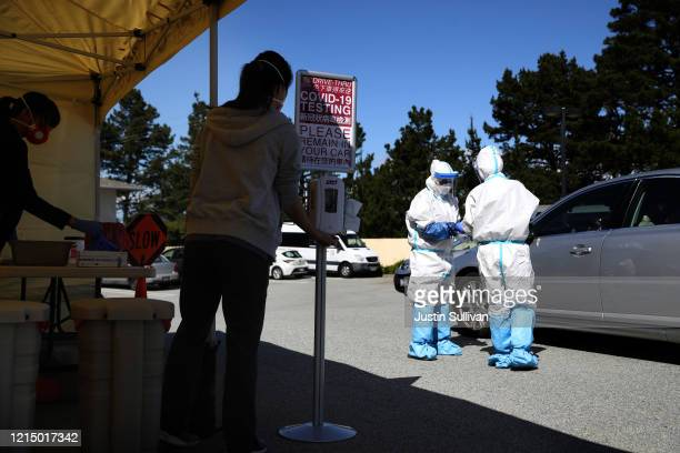 Medical professionals administer a coronavirus test during a drive-thru testing station on March 26, 2020 in Daly City, California. New coronavirus...
