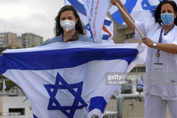 Medical professionals at Ziv Medical Centre wave Israeli natioanl flags as Israeli air force air craft fly over the hospital as they mark Israel's...