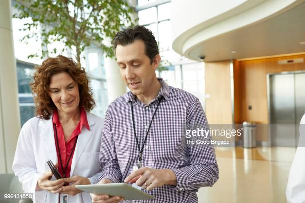 medical professionals discussing while standing in hospital lobby - administrator stock pictures, royalty-free photos & images