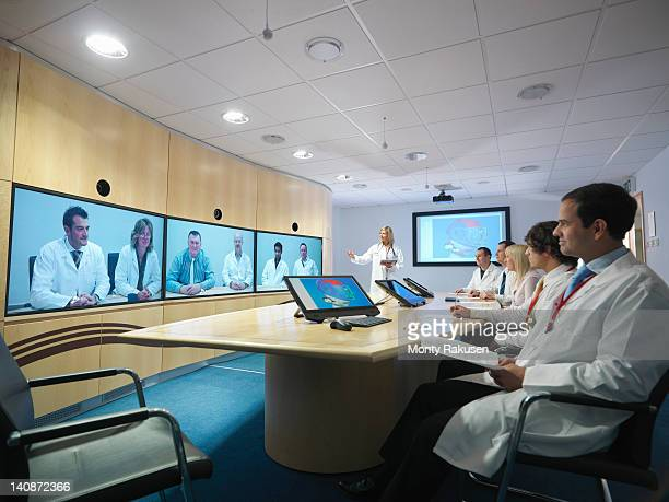 Medical professionals in meeting room taking part in video conference