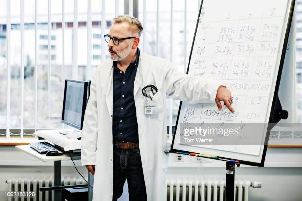 medical professor instructing students during seminar - top garment stock pictures, royalty-free photos & images