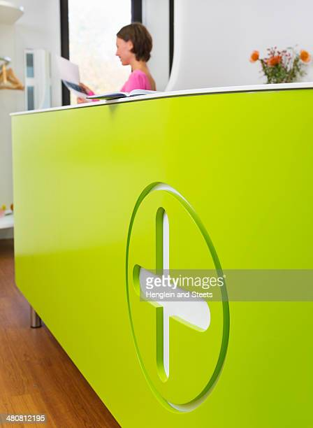Medical reception desk with woman working in background
