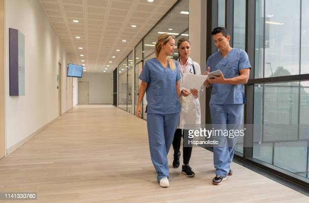 medical residents showing something to female doctor on tablet while walking at the hospital - civilian stock pictures, royalty-free photos & images