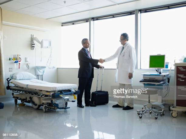 medical sales representative with doctor - descrever imagens e fotografias de stock