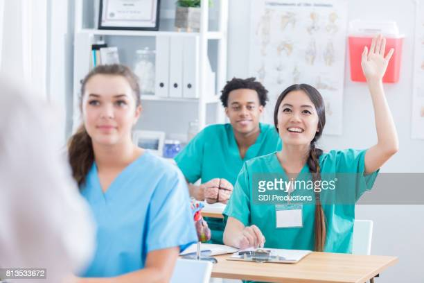 Medical school student raises hand during class