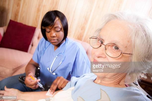 Medizinische: Senior Frau erhält eine Injektion von Zuhause healthcare Krankenschwester.