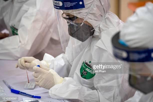 Medical specialist in protective suit works on blood samples from vendors and labourers at Long Bien market for coronavirus disease rapid test on...