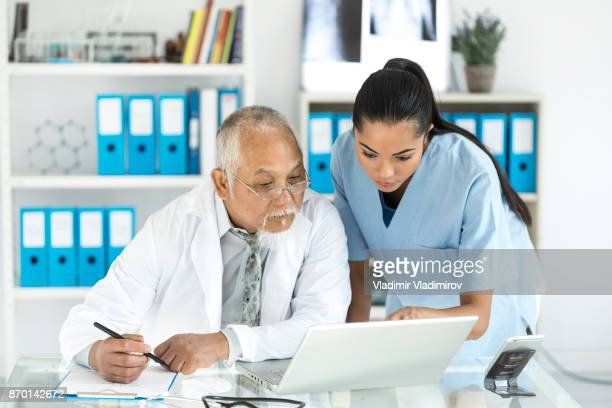 medical specialists using laptop in cabinet - instructions stock pictures, royalty-free photos & images