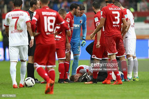 Medical staf help Dominik Kohr of Augsburg after being injured during the Bundesliga match between FC Augsburg and 1 FSV Mainz 05 at WWK Arena on...