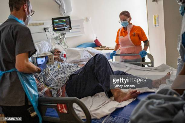 Medical staff accommodates suspected COVID -19 patient Ranghbir Hayer, who is having trouble breathing, and who has just been fit with Non-invasive...