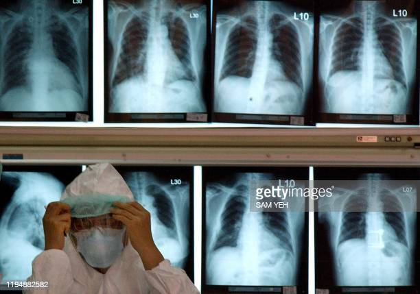 Medical staff adjusts his mask in front of patients' X-ray files at the entrance of the National Taiwan Universty Hospital in Taipei, 27 May 2003....