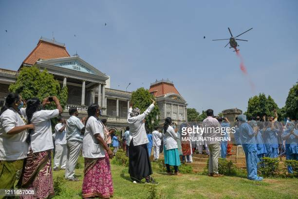 Medical staff and health workers cheer as an Indian Air Force Mi17 helicopter drops flower petals over the Victoria Hospital to pay tribute to...