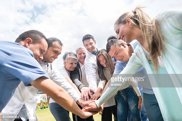 Medical staff and patients with hands together